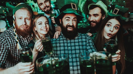 Black Bearded Man With Company. St Patrick's Day. Bar Counter. Alcohol Handling. Smiling Teenagers. Good Festive Mood. Bright Lights. Funny Club Visitors. Celebrating Together. Night Party.