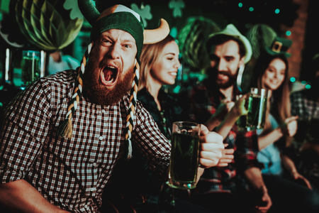 Man In Funny Hat Celebrates St Patrick's Day. Bar Counter. Alcohol Handling. Ginger Beard. Smiling Male. Good Festive Mood. Bright Lights. Funny Club Visitor. Open Mouth. Glass Of Beer. 写真素材