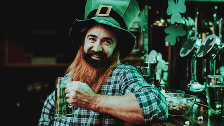 Guy In The Leprechaun Cap Is Drinking A Beer. Bar Counter. Alcohol Handling. Black Beard. Smiling Male. Good Festive Mood. Bright Lights. Funny Club Visitor. Open Mouth. St Patricks Day.