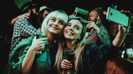 Two Girls Do Selfie In Pub. St Patrick's Day Celebrating Concept. Bar Counter. Good Festive Mood. Bright Lights. Club Visitors. Having Fun. Resting Together. Memory Photo. Smiling Women.