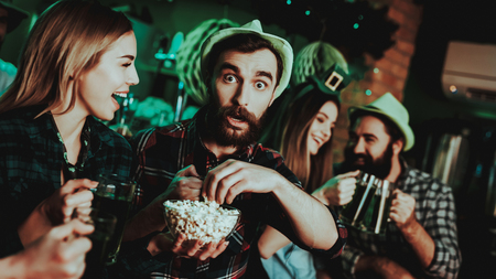 Man In Funny Hat Is Eating Popcorn With A Girl. Beer Snacks. Alcohol Handling. Black Beard. Smiling Teenagers. Good Festive Mood. Bright Lights. Club Visitors. Funny Hats. Glasses Clinking.