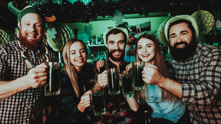 Young Company Are Celebrating St Patricks Day. Bar Counter. Alcohol Handling. Black Beard. Smiling Teenagers. Good Festive Mood. Bright Lights. Club Visitors. Funny Hats. Glasses With Beer.