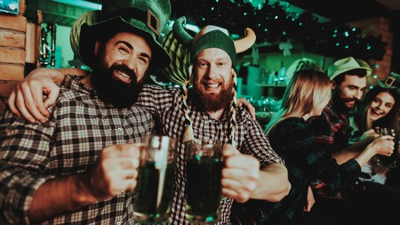 Two Men In Funny Caps. St Patricks Day Concept. Having Fun. Beer Drinking. Bar Counter. Alcohol Handling. Black Beard. Bearded Males. Good Festive Mood. Bright Lights. Funny Club Visitors.
