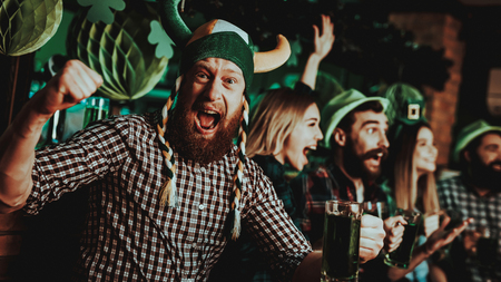 Man In Funny Hat Celebrates St Patricks Day. Bar Counter. Alcohol Handling. Ginger Beard. Smiling Male. Good Festive Mood. Bright Lights. Funny Club Visitor. Open Mouth. Glass Of Beer.