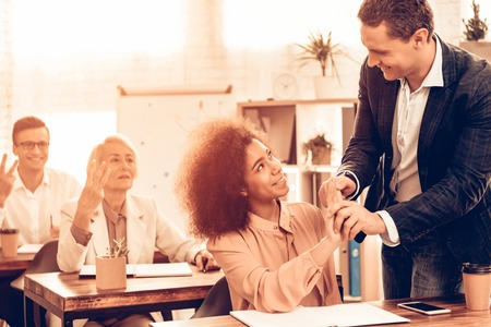 Pupils is Studying. Students is Showing Number Three Sign. Teacher is Helping a Female Student. Students is Multiracial People of Different Ages. Pupils is Sits at Tables. People Located in Classroom. Stock Photo