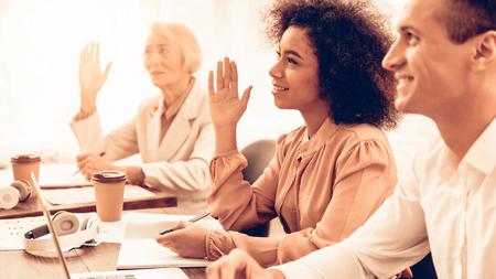Der Lehrer stellt den Schülern Fragen. Studenten sind gemischtrassige Menschen unterschiedlichen Alters. Studentinnen hebt die Hände. Studenten sitzen an Tischen. Personen im Klassenzimmer.