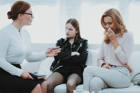 Upset Teenage Daughter in Jacket in Psychologist Office with Mother. Punk in Lather Jacket. Communication Concept. Psychotherapy Concept. Puberty Problems. Conflict in Family. Family Doctor. Stok Fotoğraf