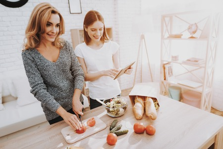 Smiling Mother and Daughter Cooking Together in Kitchen. Relationship in Family. Holiday at Home. Healthy Food and Lifestyle Concept. Cooking Together. Happiness in Family Concept.