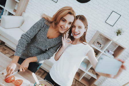 Smiling Mother and Daughter Taking Selfie in Kitchen. Relationship in Family. Holiday at Home. Healthy Food and Lifestyle Concept. Cooking Together. Happiness in Family Concept. Taking Photo.