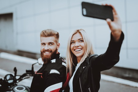 Man And Woman Doing Selfie Sitting On A Bike. Going For Ride. Fashion Riders. Confident Staring. Speed Vehicle. Biker With A Beard. Motorbike Concept. Classic Style. Ready To Drive. Tripping Together.