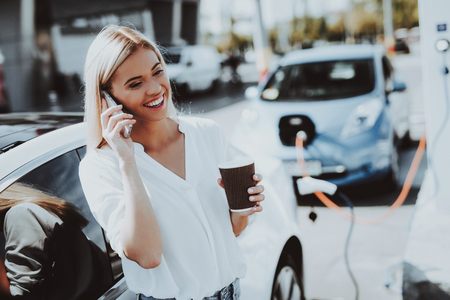 Car Charge Concept. Girl Talks The Phone. Automobile Station. Innovation Technology. New Generation Electro Hybrid Vehicle Plugin. Ecology Station. Futuristic Power. Cup Of Coffee.