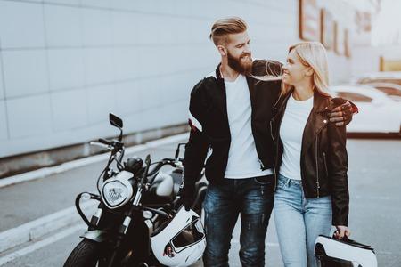 Mann und Frau Biker mit Helm. Motorradkonzept. Bereit zum reiten. Klassischer Stil. Zusammen stolpern. Straßenfahrzeug. Reisetransport. Fahrerpaar. Jeans und Jacken. Sonniger Tag.