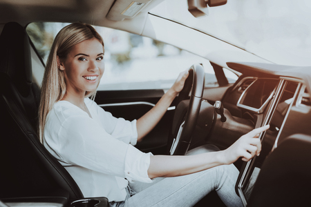 Woman In Car. Behind The Wheel Concept. Innovation Technology. New Generation Electro Hybrid Vehicle. Luxury Design. Futuristic Power. Hand On Display. Inside View. Front Seat.