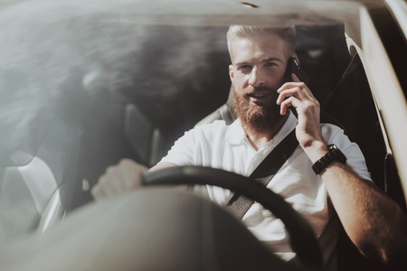 Man Has A Phone Call Behind The Wheel Of Tesla Car. Innovation Technology. New Generation Electro Hybrid Vehicle. Luxury Design. Futuristic Power. Front Seat. Behind The Glass View.