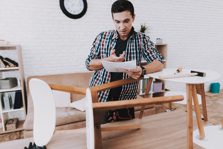 Young Man Assembling Coffee Table and Stools. Furniture Fittings. Engineer with Tool. Young Man at Home. Wooden Coffee Table. Selfmade Furniture. Man and Hobby. White Table in Room. Standard-Bild