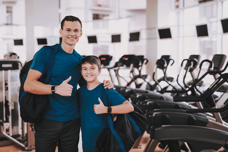 Young Father and Son near Treadmills in Modern Gym. Healthy Lifestyle Concept. Sport and Training Concepts. Modern Sport Club. Sport Equipment. Family Sport. Running Tracks. Parent with Child. Zdjęcie Seryjne