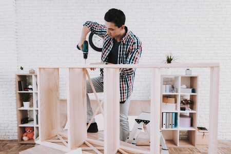 Young Man Assembling Wooden Bookshelf at Home. Wooden Bookcase. Selfmade Furniture. Homemade Decoration. Modern Furniture. Stock Photo