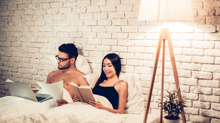Couple Using Laptop Reading Book Before Sleeping. Young Guy Watching Movie or Browsing Internet. Girl Reading Book at Night. Relationship Concept. Wife and Husband. Stock fotó