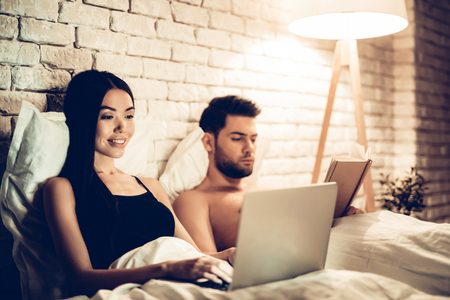 Couple Using Laptop Reading Book Before Sleeping. Young Guy Watching Movie or Browsing Internet. Girl Reading Book at Night. Relationship Concept. Wife and Husband. Фото со стока