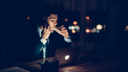 Confident Businessman Working in Office at Night. Closeup Businessman Working Laptop Office at Night. Worker Working Overtime. Eating Sandwich. Talking Mobile Phone. Business Concept.