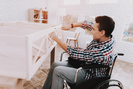 Young Man on Wheelchair Assembling Wooden Bookshelf at Home.