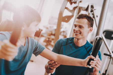 Young Father and Son Doing Exercises in Sport Club.