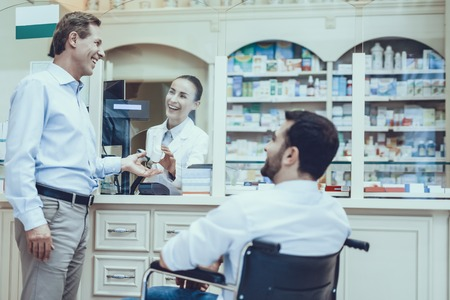 Female Pharmacist Selling Bottle with Pills. Other Man Sits in Wheelchair and Waits. Stock Photo