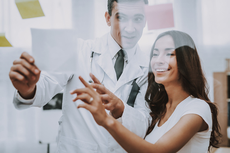 Doctor is Showing a Stickers on Glass to Woman.