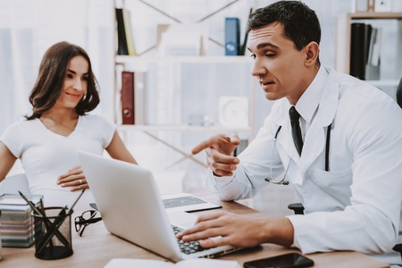 Doctor Pointing Something on Laptop. Stock Photo