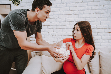 Young Man Takes a Marshmallow from His Wife. Stock Photo