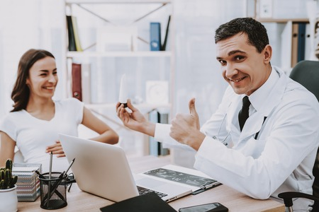 Doctor is Showing a Cream for Belly to Woman Showing OK Sign.