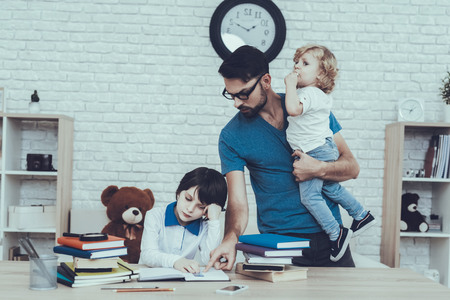 Father is Doing a Homework with Eldest Son. Man is Holding a Younger Son in Arm. Reklamní fotografie - 115744057