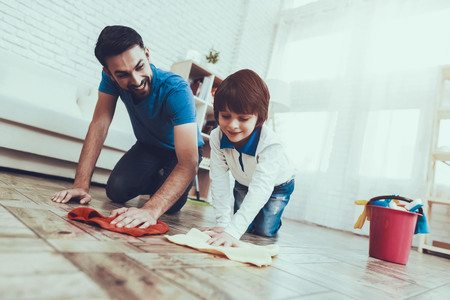 Padre e hijo lavando el piso con trapos.