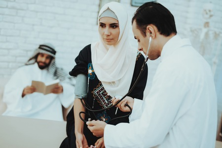 Arabic Doctor Checking Heartbeat of a Muslim Woman. Stock Photo