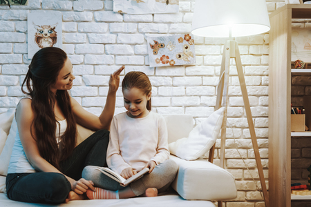 Mother with Daughter is Sitting on Couch. Daughter is Reading a Book. Mother Stroking Her Daughter. Persons is Smiling. Wall with Pictures on Background. Evening Time. Home Interior.
