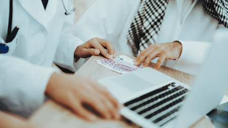 Close Up Arabic Patient Giving Money to Doctor. Corruption Concept. Man Giving Dollars To Doctor. Payment. Salary Time. Reception of Therapist. Discussing Diagnosis. Examination. Medical Concept.