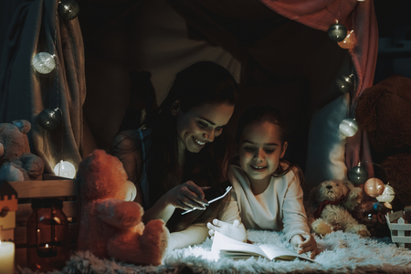 Mother and Daughter Lying on Carpet Under the Fake Tent. Mother and Daughter is Reading a Book. Mother Shines on the Book with a Mobile Phone. Persons is Smiling. Evening Time. Home Interior.
