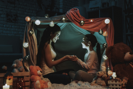 Mother and Daughter is Lying on Carpet. Persons is Lying Under the Fake Tent. Mother and Daughter is Holding a Light in Hands. People is Looking at Each Other and Smiling. Evening Time. Home Interior.