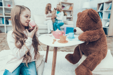 Young Girl Playing with Big Plush Bear at Home. Smiling Women. Sitting on Sofa. Happy Family. Sitting at Home. Tea Party at Home. Small Table. White Carpet. Girl with Cup. Fun Indoor.