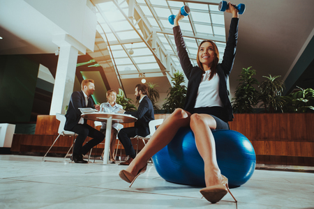 Corporate Sport Lifestyle. Healthcare of Business People. Worker Relax in Office . Yoga Practice. Happy Office Manager. Woman Balance on Ball with Dumbbells . Girl Stretching on Work.