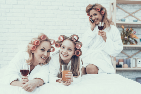 Women in White Bathrobes with Drink in Glasses. Have Fun at Home. Happy Family. Mother with Daughter. Smiling Women. Lying on Sofa. Have Fun Indoor. White Sofa. Family after Bath. Women's Beauty Concept. Banque d'images - 115380244