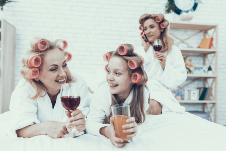 Women in White Bathrobes with Drink in Glasses. Have Fun at Home. Happy Family. Mother with Daughter. Smiling Women. Lying on Sofa. Have Fun Indoor. Family after Bath. Women's Beauty Concept. Banque d'images - 115665188