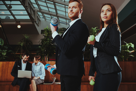 Corporate Sport Lifestyle. Healthcare of Business People. Office Workers Working with Dumbbells. Workers doing Fitness Exercises. Yoga Practice. Employees Practicing on Bench in Office.
