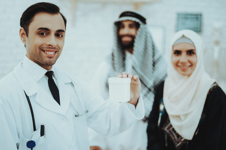 Smiling Arabic Family and Doctor Looking in Camera. Doctor Holding Medical. Consultation at Clinic. Reception of Therapist. Discussing Diagnosis. Examination. Medical Concept. Arabian Concept. Standard-Bild