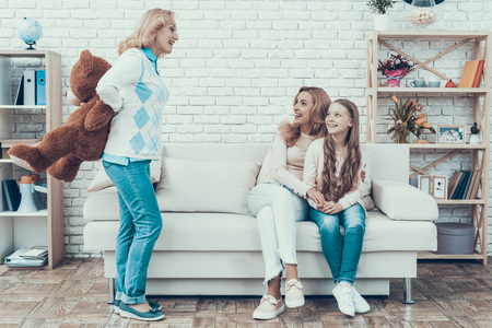 Mother Presenting Toy Bear to Smiling Daughter. Gift on Birthday. Mother with Daughter. Smiling Women. Sitting on Sofa. Celebration Concept. Happy Family. Sitting at Home. Holiday in March. Stock Photo