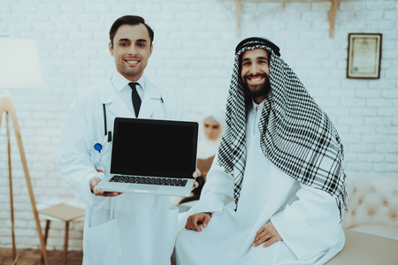 Male Doctor Consulting Arabic Man at Hospital. Doctor Explaining Diagnosis with Tablet. Consultation at Clinic. Reception of Therapist. Discussing Diagnosis. Examination. Medical Concept.