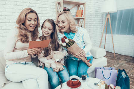 Family Celebrating Mothers Birthday at Home. Cake on Table. Happy Family. Mother with Daughter. Smiling Women at Home. Smiling Grandmother. Celebration Concept. Cup of Tea. Toy Bear. Фото со стока