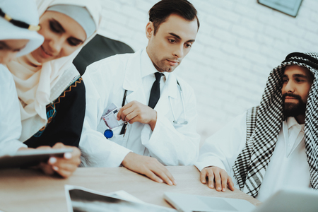 Arabic Patient Giving Euros Money to Doctor. Corruption Concept. Man Giving Dollars To Doctor. Payment. Salary Time. Reception of Therapist. Discussing Diagnosis. Examination. Medical Concept.