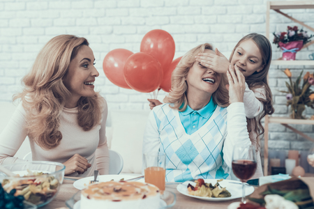 Family Preparing Surprize for Grandmother at Home. Cake on Table. Happy Family. Mother with Daughter. Smiling Women. Smiling Grandmother. Celebration Concept. Glass of Wine. Closed Eyes. Red Baloons.