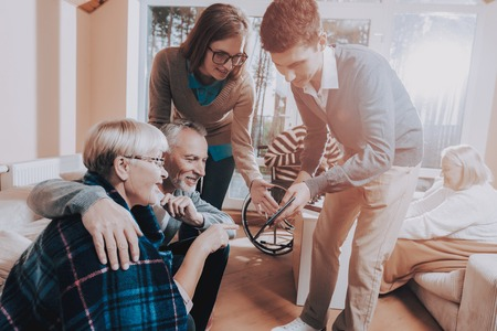 Nursing Home. Senior Couple Hold Lees of Life. Young People Visit Older. Sear and Yellow Leaf. Man and Woman Watch Something on Tablet. Meeting with Grandchildren. Grandchildren Hold Laptop.